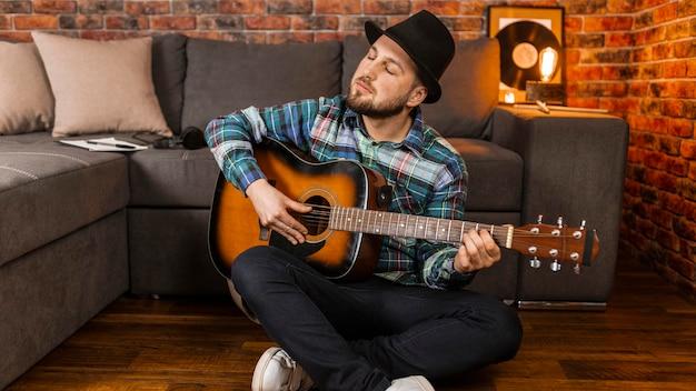 Volledig geschoten man met hoed gitaar spelen