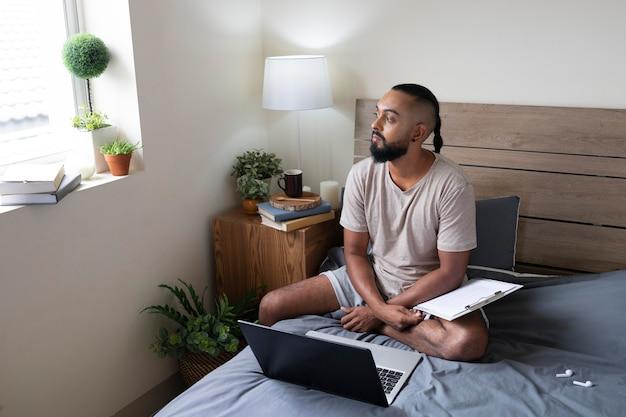 Volledig geschoten man met laptop in bed