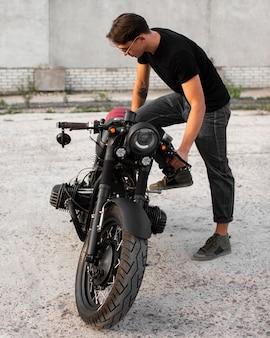 Volledig geschoten man met oude motorfiets