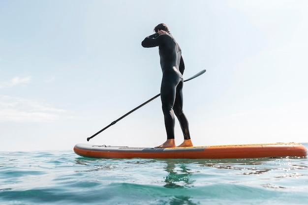 Volledig geschoten man met pak op surfplank