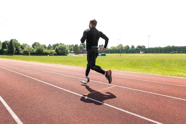 Volledig geschoten man met prothese die op de atletiekbaan loopt running