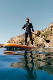 Volledig geschoten man op surfplank