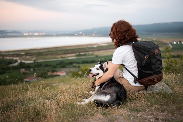 Volledig geschoten man zit met hond in de natuur