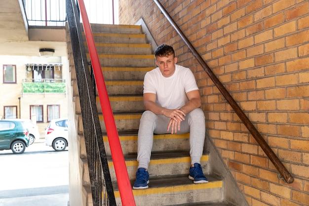 Volledig geschoten man zittend op trappen