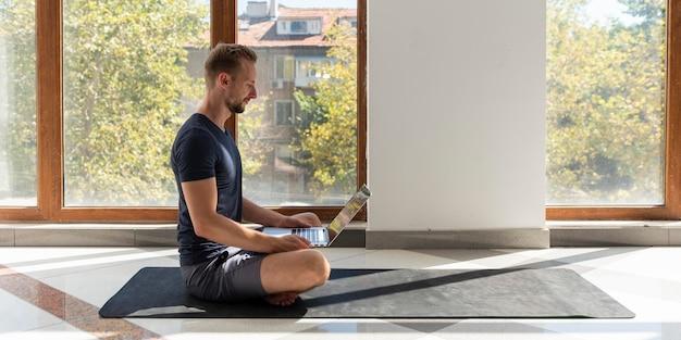 Volledig geschoten man zittend op yoga mat met laptop