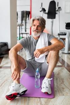 Volledig geschoten man zittend op yoga mat