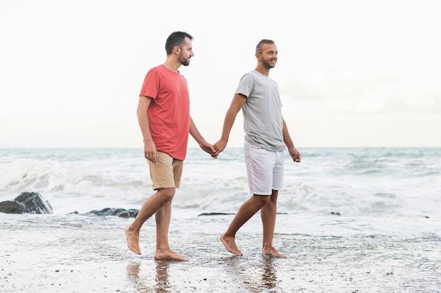 Volledig geschoten mannen die op strand lopen