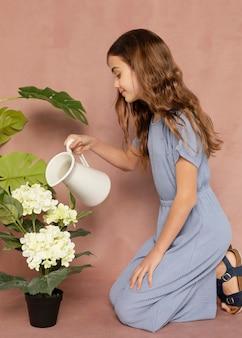 Volledig geschoten meisje dat bloemen water geeft
