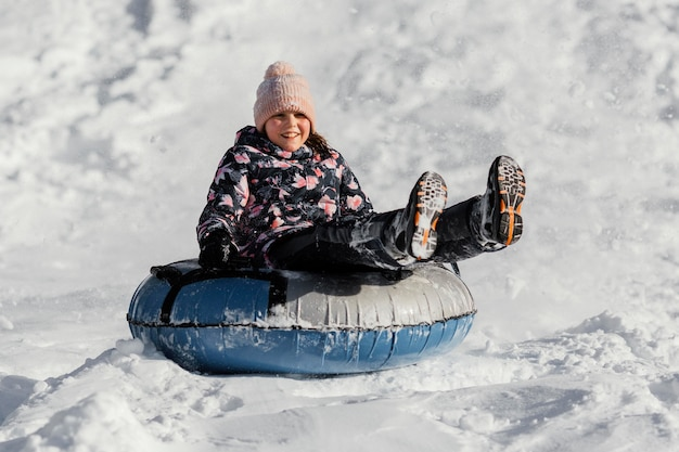 Volledig geschoten meisje dat in sneeuw speelt