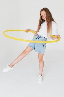 Volledig geschoten meisje dat met cirkel speelt
