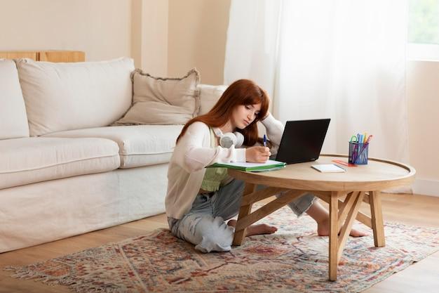 Volledig geschoten meisje dat met laptop op vloer leert