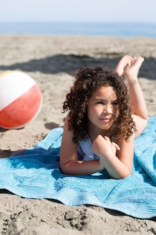 Volledig geschoten meisje dat op strand ligt