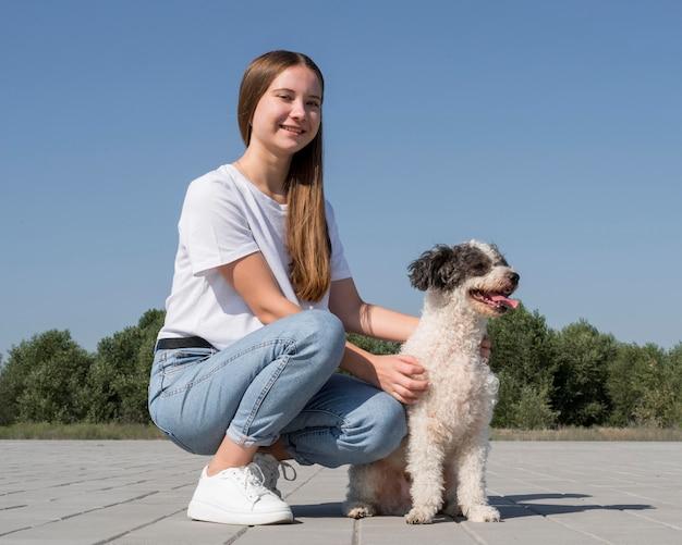 Volledig geschoten meisje dat schattige hond aait