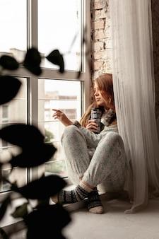 Volledig geschoten meisje dat uit het raam kijkt
