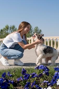 Volledig geschoten meisje en schattige hond buitenshuis