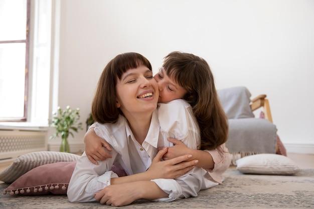 Volledig geschoten meisje kussende moeder