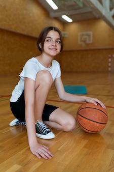 Volledig geschoten meisje met basketbal