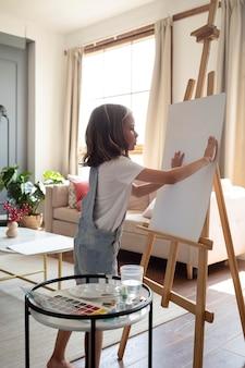 Volledig geschoten meisje met canvas