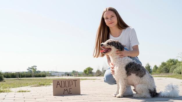 Volledig geschoten meisje met hond en adopteer me teken
