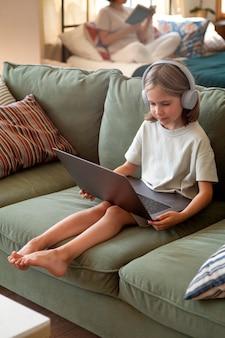 Volledig geschoten meisje met laptop op bank