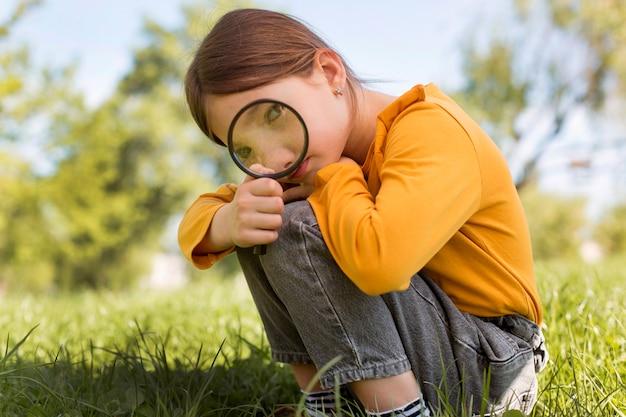 Volledig geschoten meisje met vergrootglas