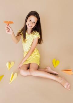 Volledig geschoten meisje poseren met papieren vliegtuigjes
