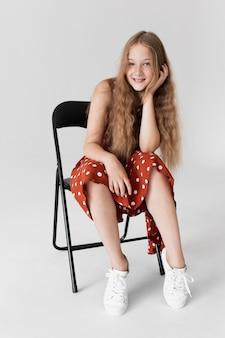 Volledig geschoten meisje poseren op stoel