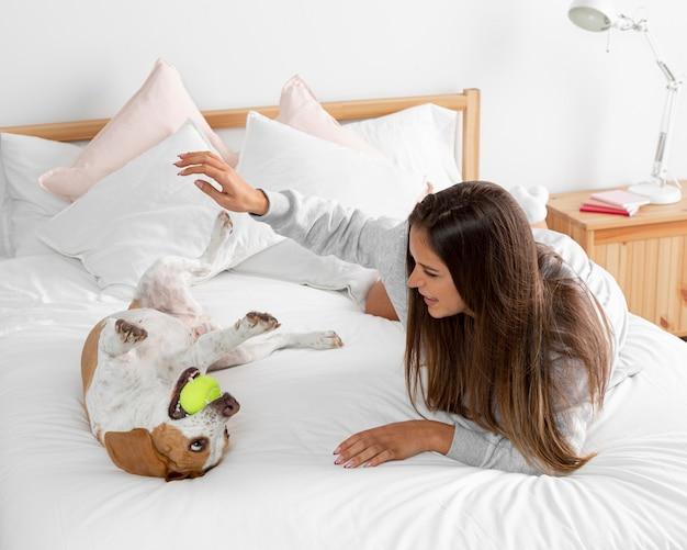 Volledig geschoten meisje speelt met hond