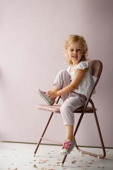 Volledig geschoten meisje zittend op een stoel