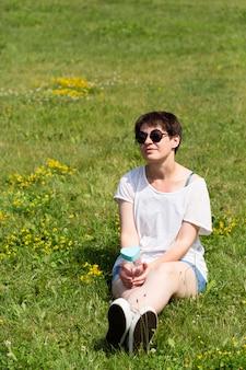 Volledig geschoten meisje, zittend op het gras