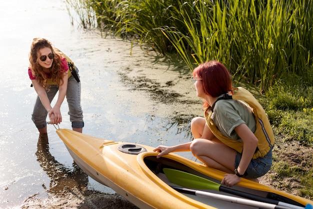 Volledig geschoten meisjes die kajak uit het water halen