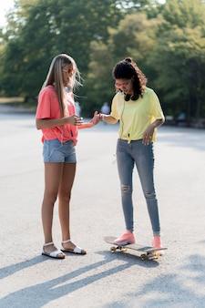Volledig geschoten meisjes met skateboard