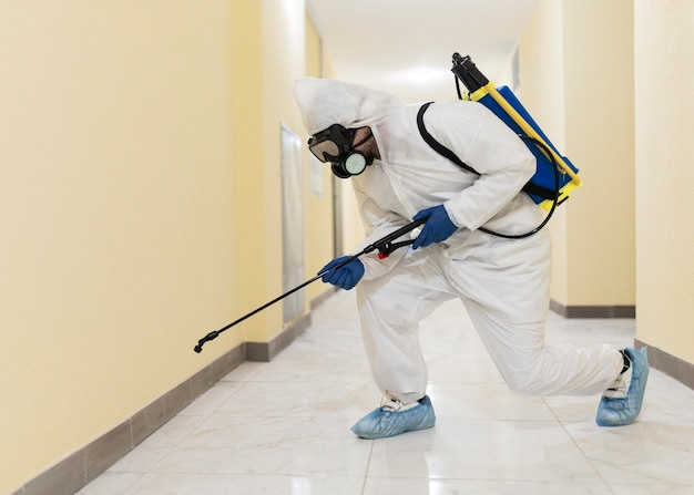 Volledig geschoten mens die gebouw desinfecteert