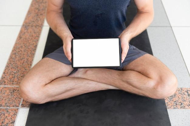 Volledig geschoten mens op yogamat met lege tablet