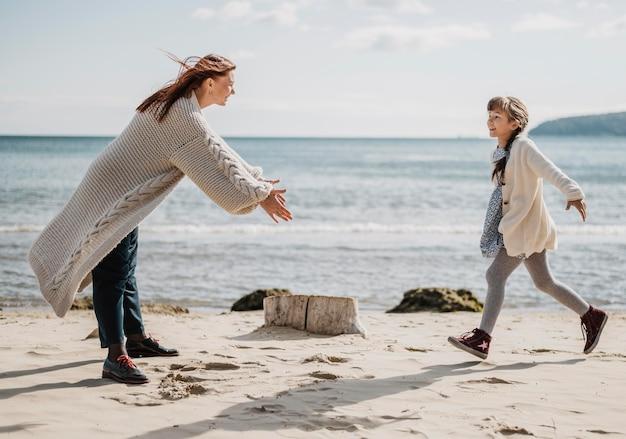 Volledig geschoten moeder en dochter op strand