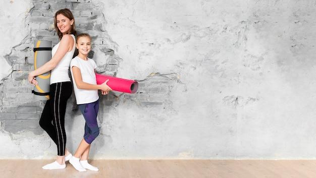 Volledig geschoten moeder en kind die yogamatten met exemplaar-ruimte houden