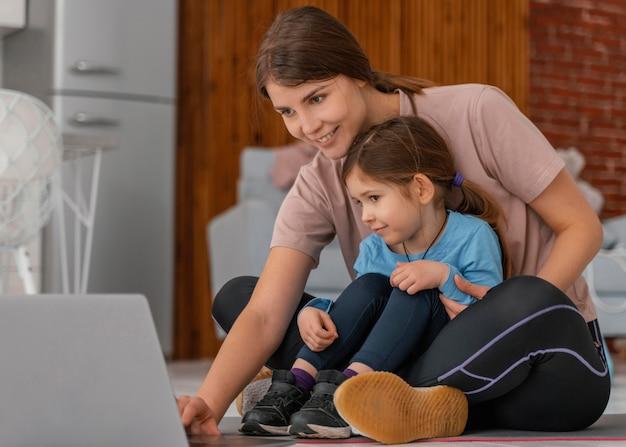 Volledig geschoten moeder en kind kijken naar laptop