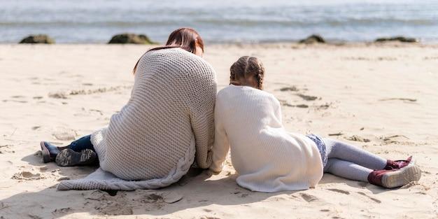 Volledig geschoten moeder en kind zittend op zand