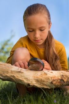 Volledig geschoten nieuwsgierig meisje dat blad observeert