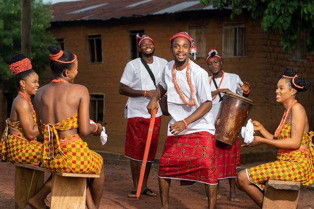 Volledig geschoten nigeriaanse mensen die buitenshuis vieren
