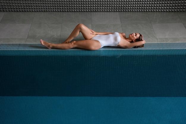 Volledig geschoten ontspannen vrouw die dichtbij pool ligt
