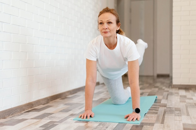 Volledig geschoten oude vrouw die yoga doet