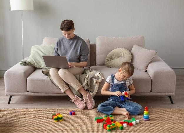 Volledig geschoten ouder aan het werk en kind aan het spelen