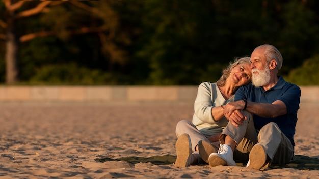 Volledig geschoten paar dat op zand zit Gratis Foto