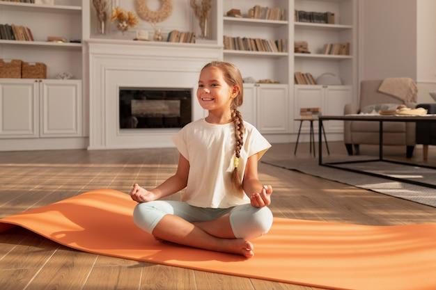 Volledig geschoten smileykind mediterend op yogamat