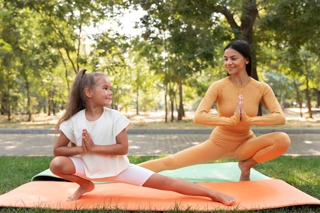 Volledig geschoten smileymeisje en vrouw die yoga doen