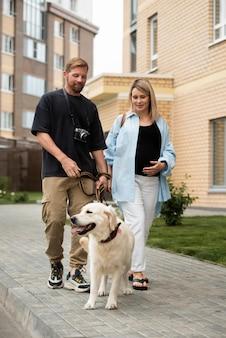 Volledig geschoten smileypaar dat met hond loopt