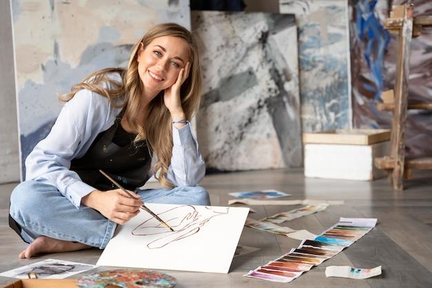 Volledig geschoten smileyvrouw die op canvas schilderen