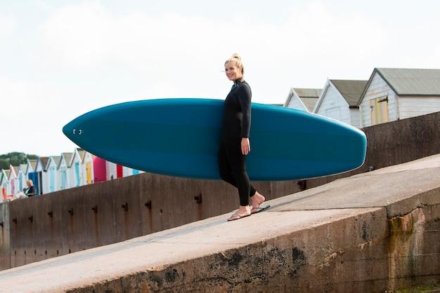 Volledig geschoten smileyvrouw die paddleboard draagt