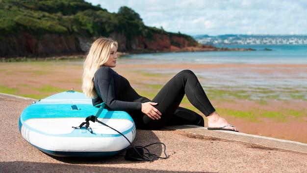 Volledig geschoten smileyvrouw met paddleboard